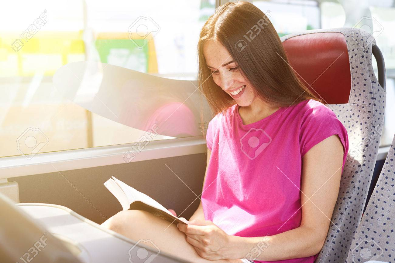 smiley woman reading book in the bus - 41979492