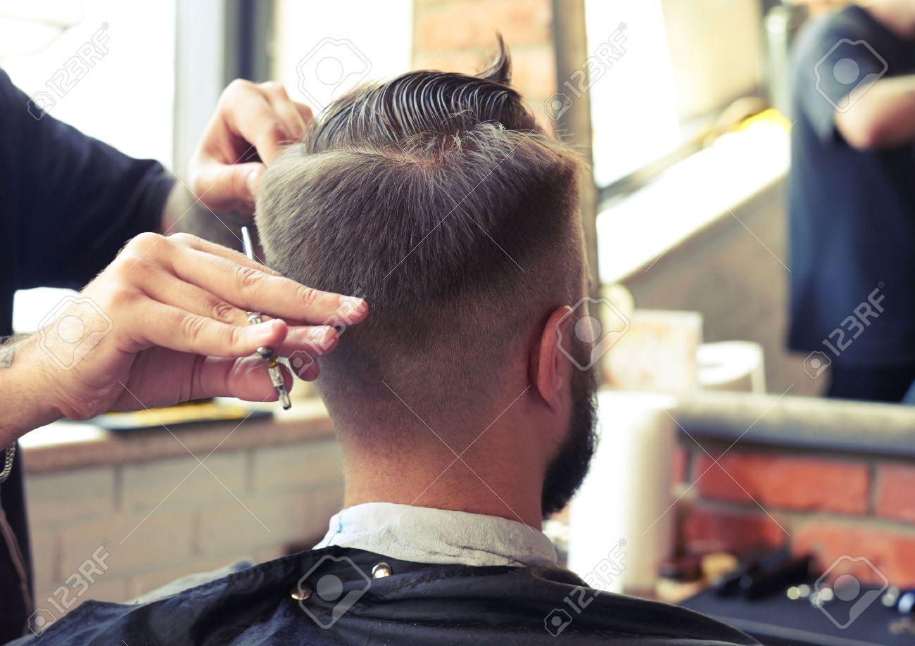 Banque d\u0027images , vue de dos de l\u0027homme dans un salon de coiffure. coupe de  cheveux avec des ciseaux de coiffeur