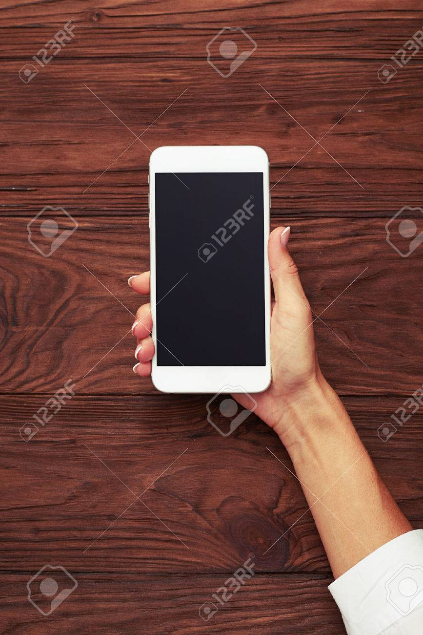 view from above on womans hand with smartphone over wooden background - 46201333
