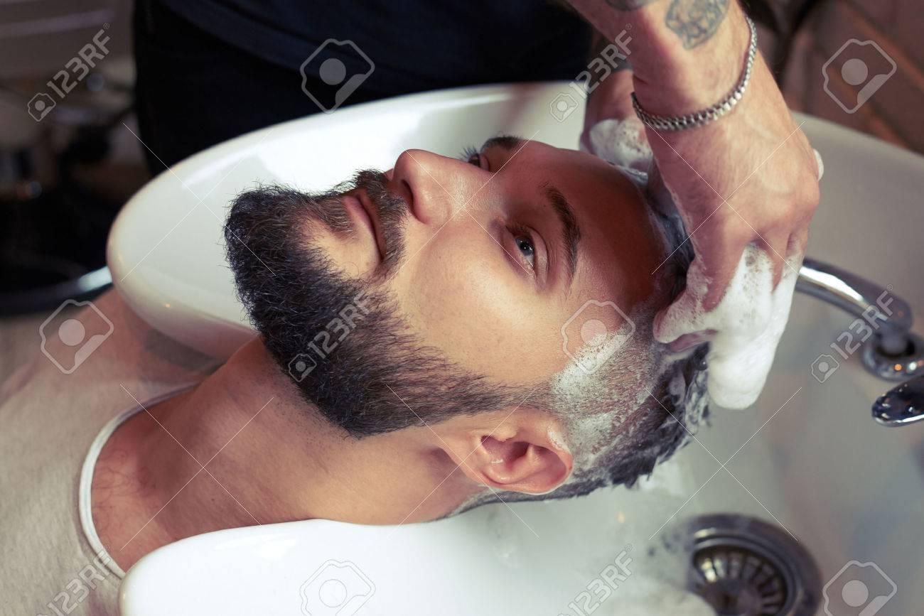 barber washing man head in stylish barbershop - 46201443