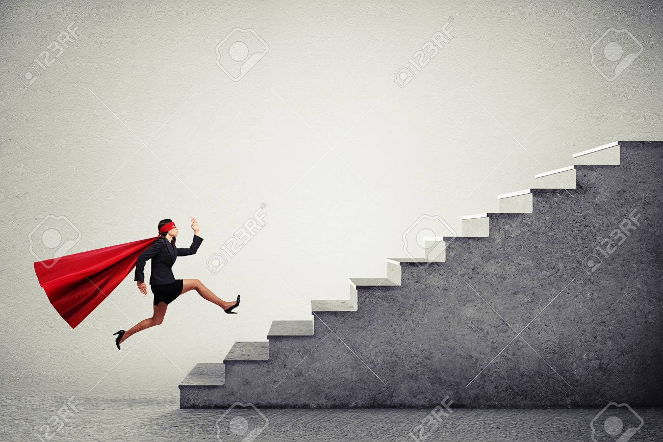 purposeful superwoman in red cloak running up stairs over light grey background - 49452648
