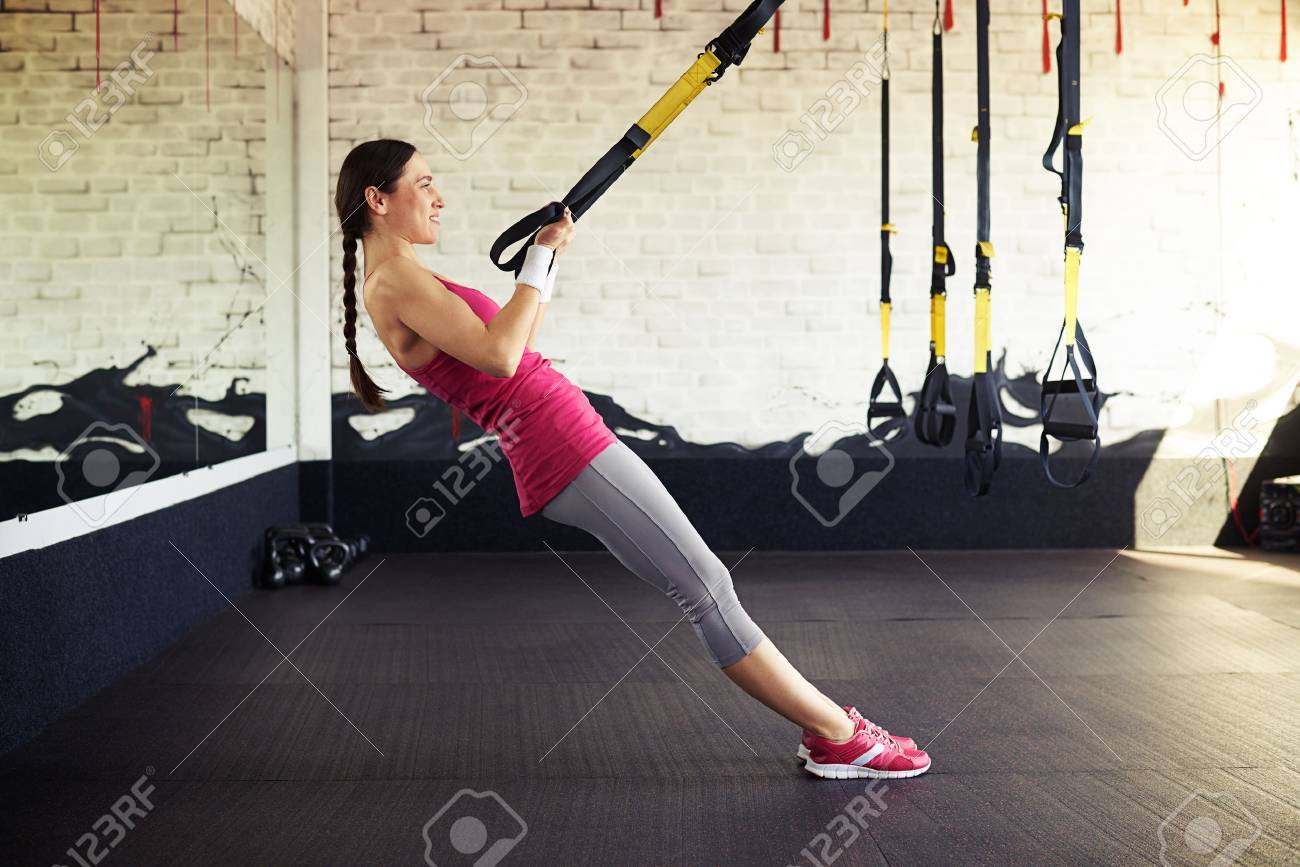 detailed pictures 67771 dbdf3 Stock Photo - Young smiling girl in sportswear is pushing at the trx