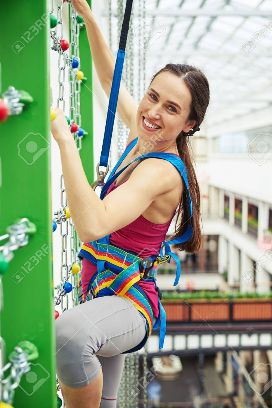 Sportswoman in safety equipment is smiling while climbing on the wall with  chains in indoor rock 2cb3ca5ed