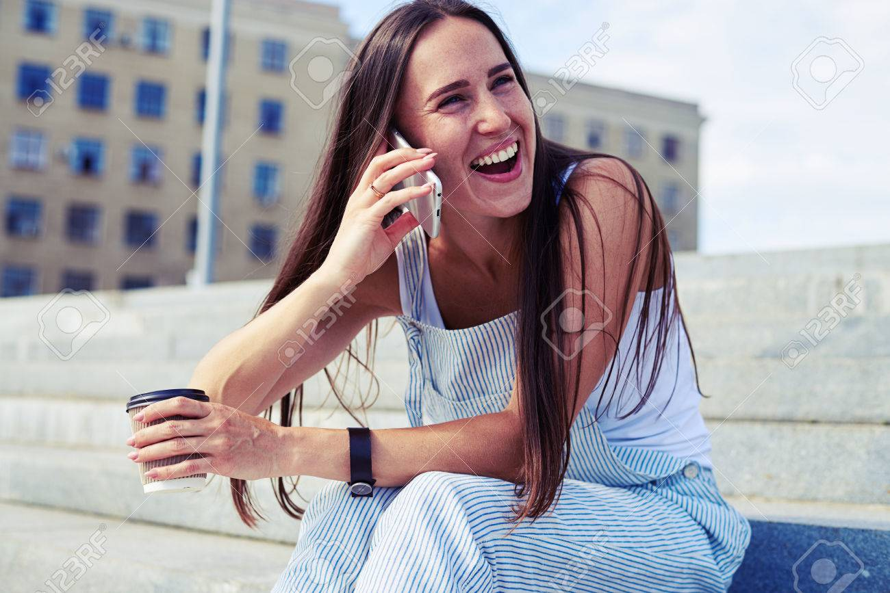 Sexy stylish female is laughing on a joke during her phone talk while  having a coffee