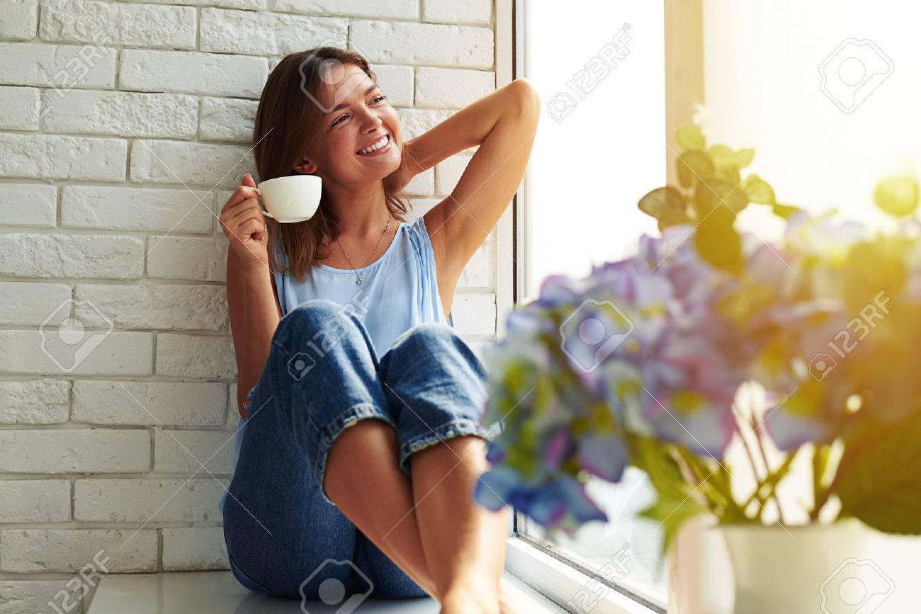 The perfect morning relation with a cup of aroma coffee. Young girl in a casual stylish suit basking in the peaceful atmosphere. She looks calm, happy and relaxed while sitting on the window-sill. - 62818441