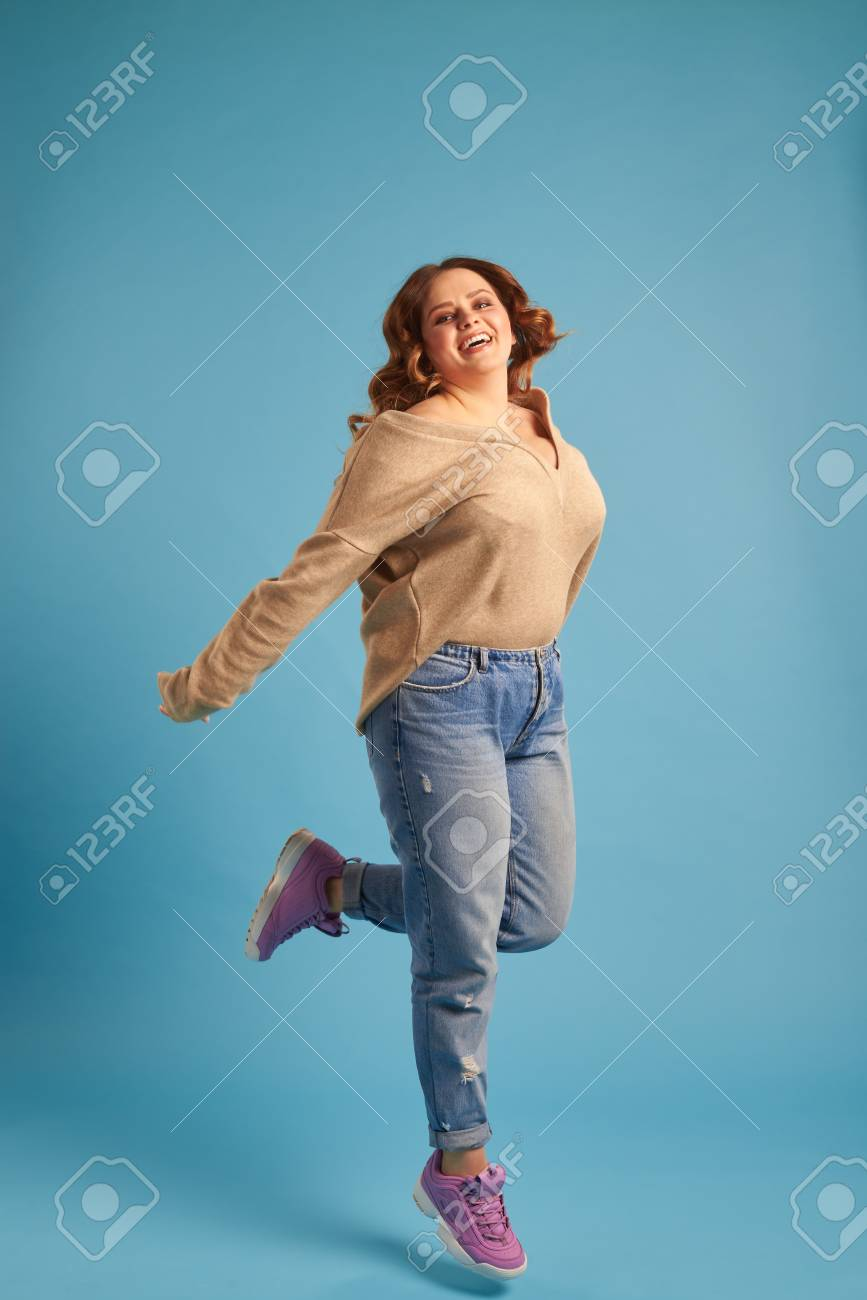 914368b10a1 Plus-size woman jumping in excitement at studio Stock Photo - 101927007