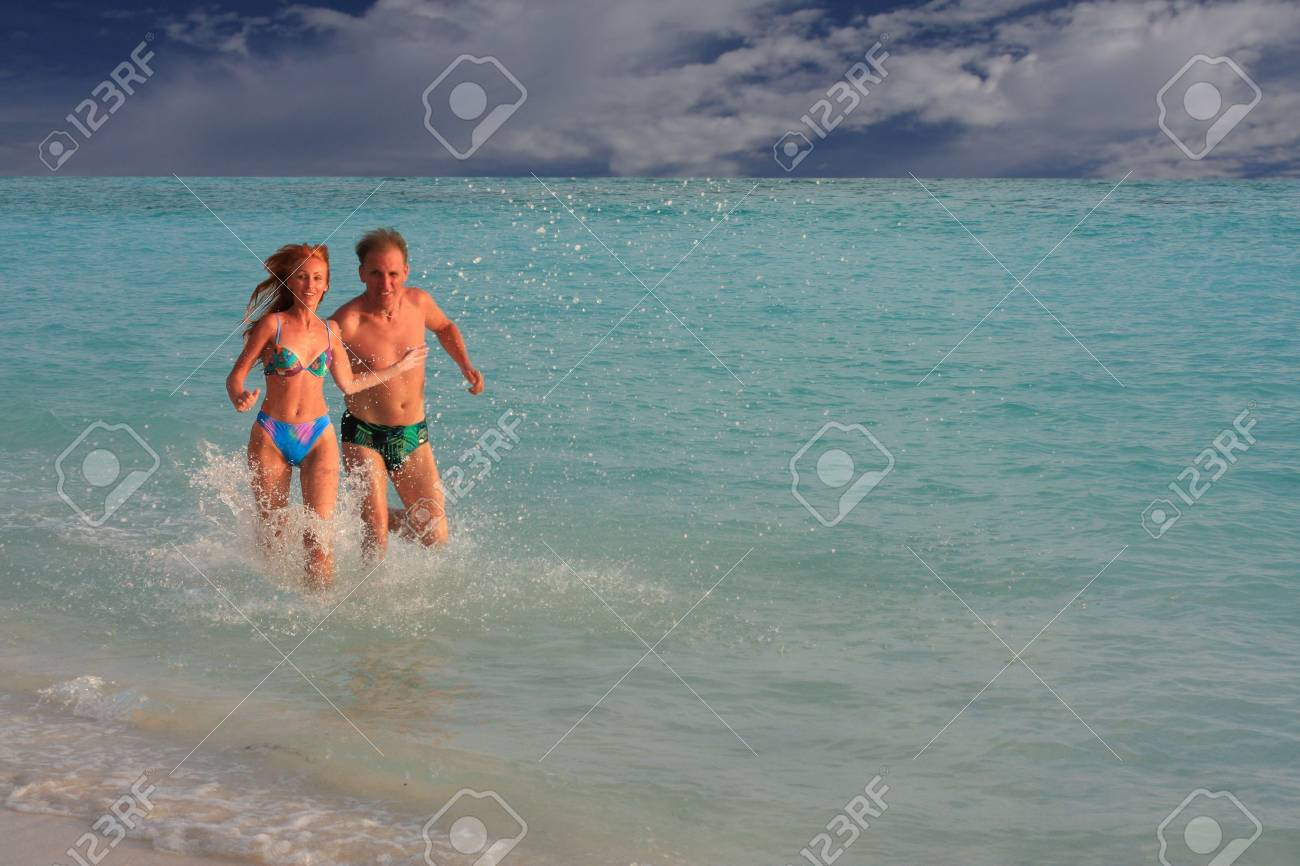 Men and woman runs along ocean coast on water Stock Photo - 4810184