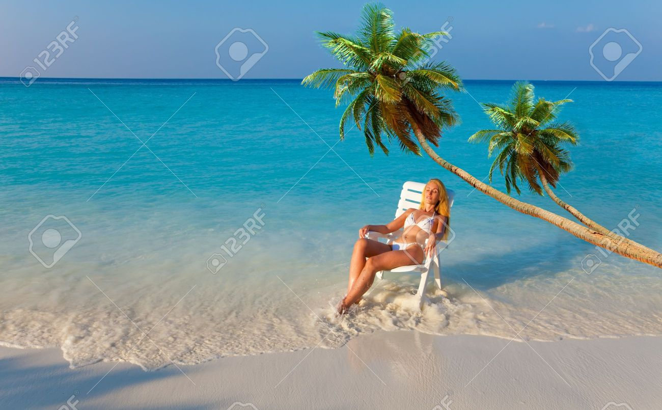 The girl in a chaise lounge at ocean under palm trees on a sunset Stock Photo - 9139535