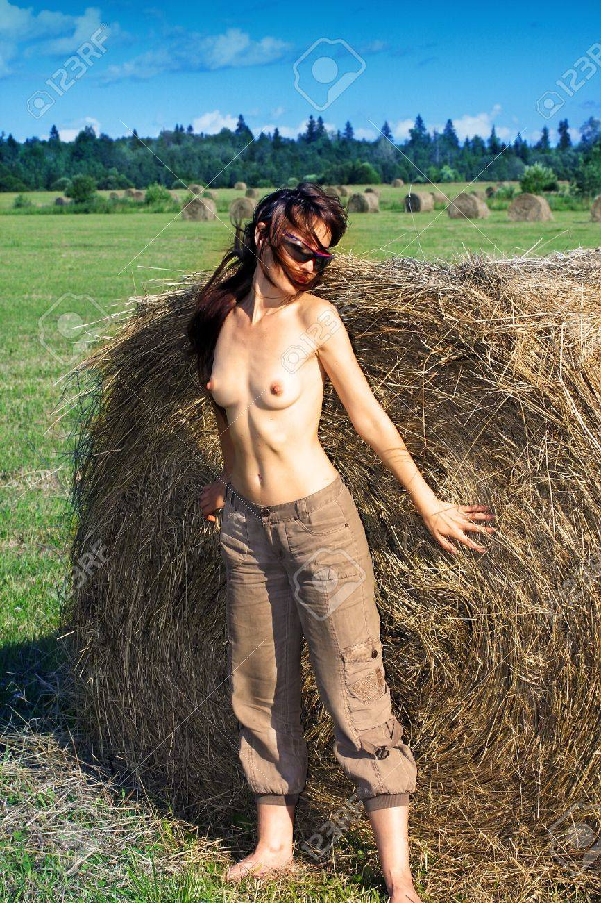 The nude woman in the field near to a haycock. Stock Photo - 9997479