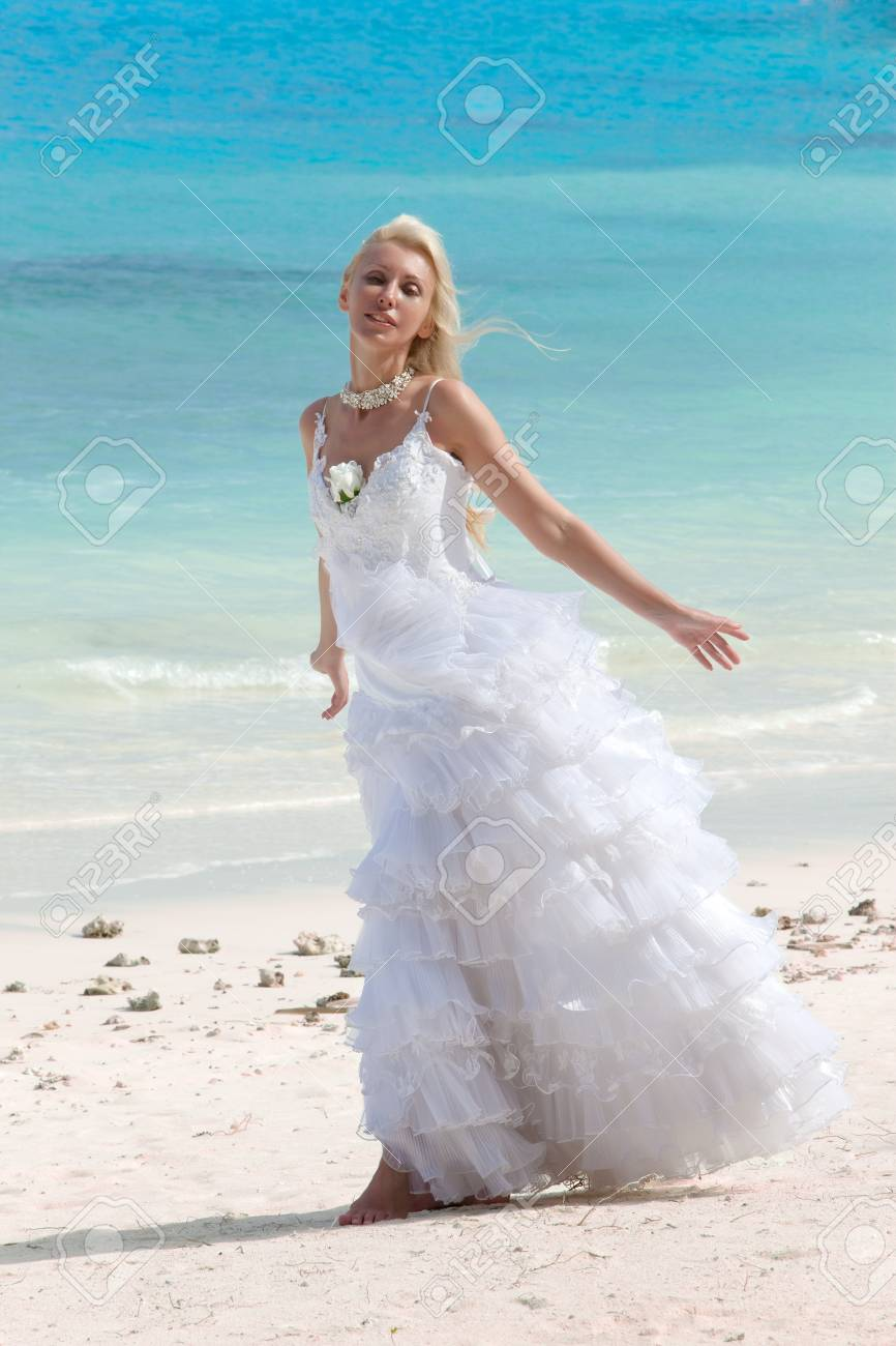 The young beautiful woman in a dress of the bride standing at sea edge Stock Photo - 12368976