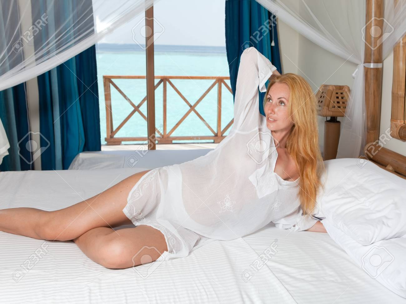 Young pretty woman in bed with ocean behind window. Stock Photo - 17456637