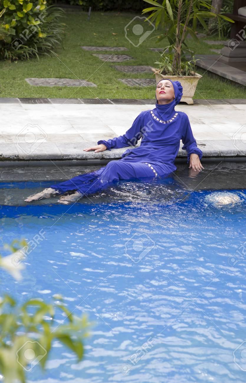 f303e387746 attractive woman in a Muslim swimwear burkini sits on the edge..