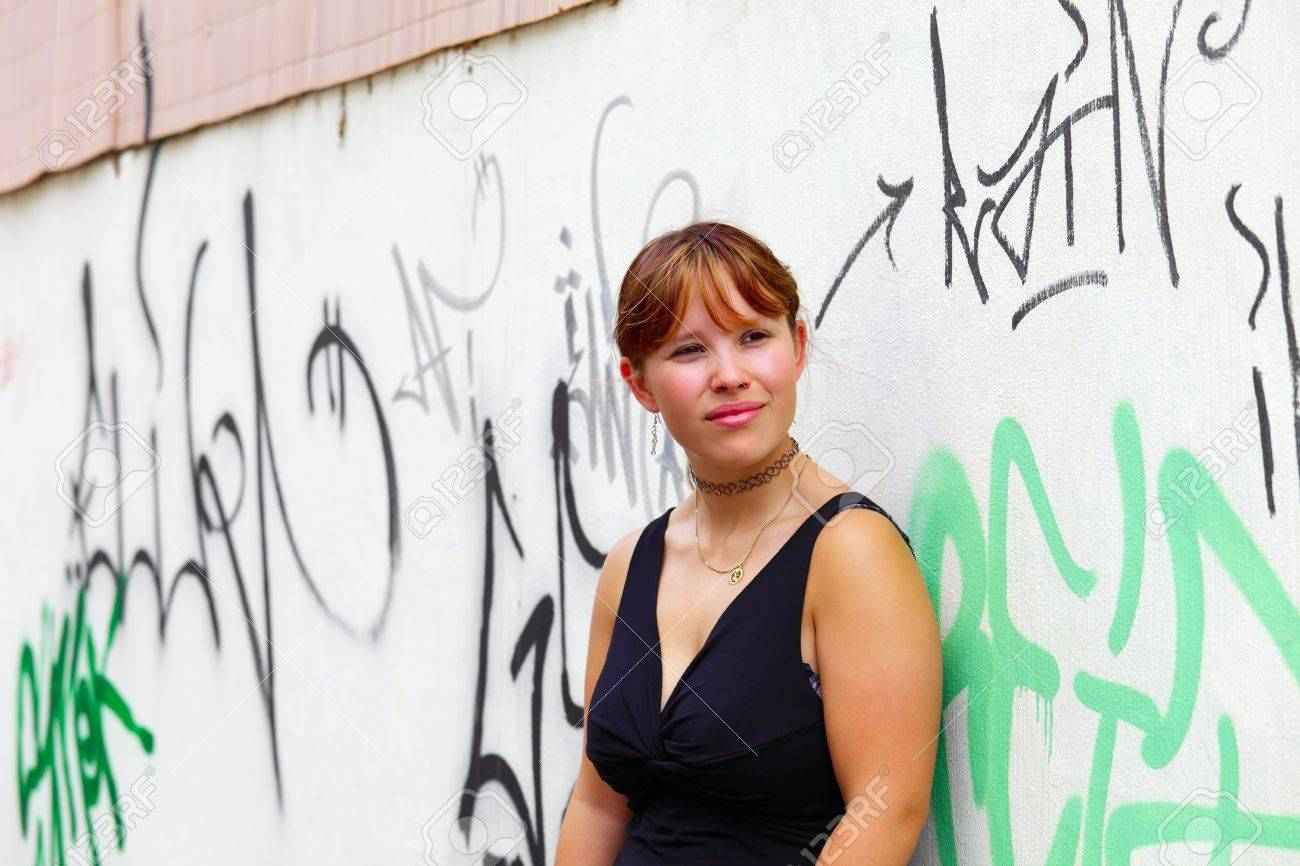 Portrait of a young woman in the background a white  wall with graffiti,  in small city Saarlouis, Saarland / Germany Stock Photo - 14295437