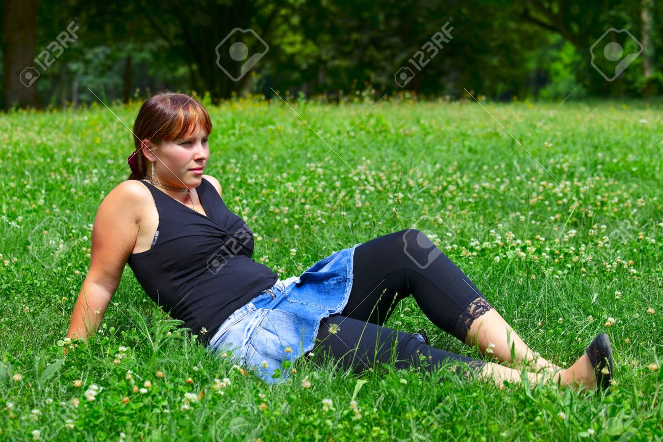 A young woman sits on a green meadow in the sun, outdoor in a small city Saarlouis. Saarland / Germany Stock Photo - 14722540