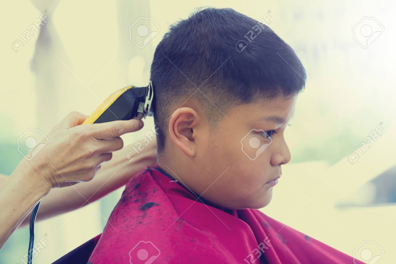 Barber Shop Hairdresser Makes Hairstyle To A Asian Boy With Stock