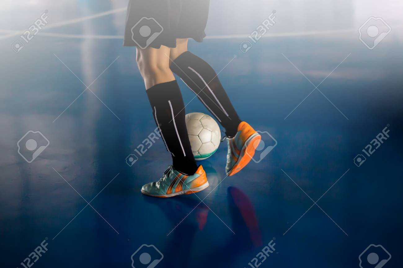 Futsal player trap and control the ball for shoot to goal. Soccer players fighting each other by kicking the ball. Indoor soccer sports hall. Football futsal player, ball, futsal floor. Sports background. Youth futsal league. Indoor football players with classic soccer ball. - 110672619