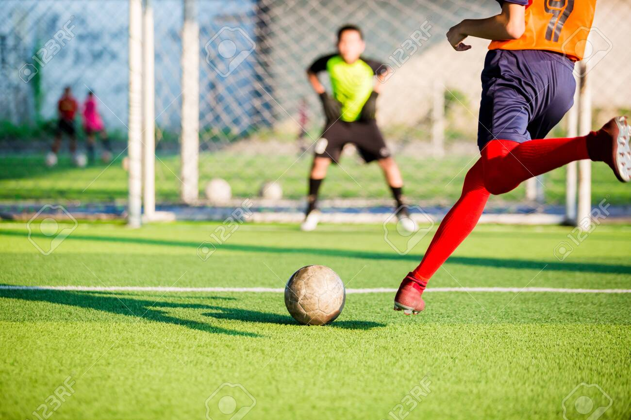 soccer player run to shoot ball at penalty kick to goal with blurry goalkeeper background, concept of making goals and protection - 120398938