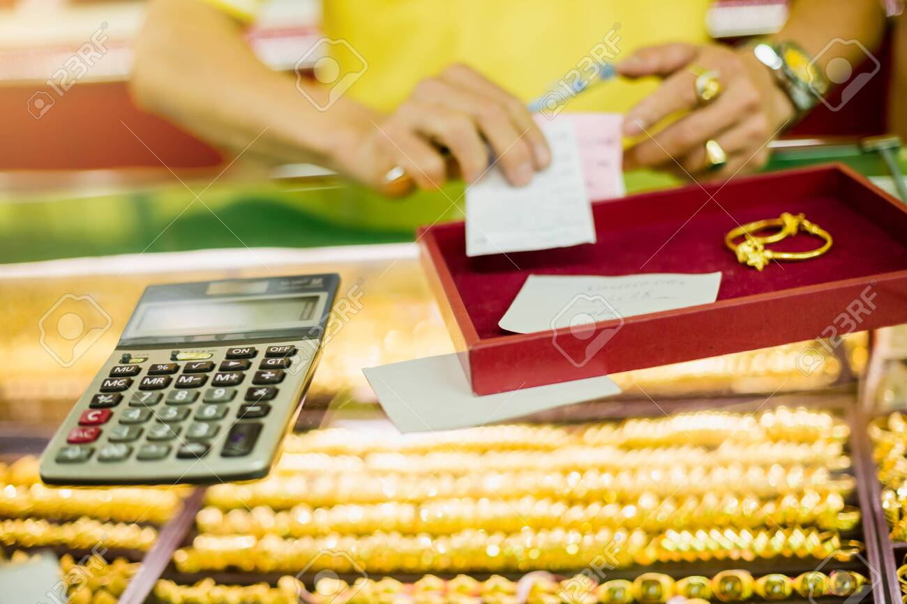 the calculator to calculate the purchase of gold jewelry with sale blurry staff holding ticket in the gold shop. - 125677366