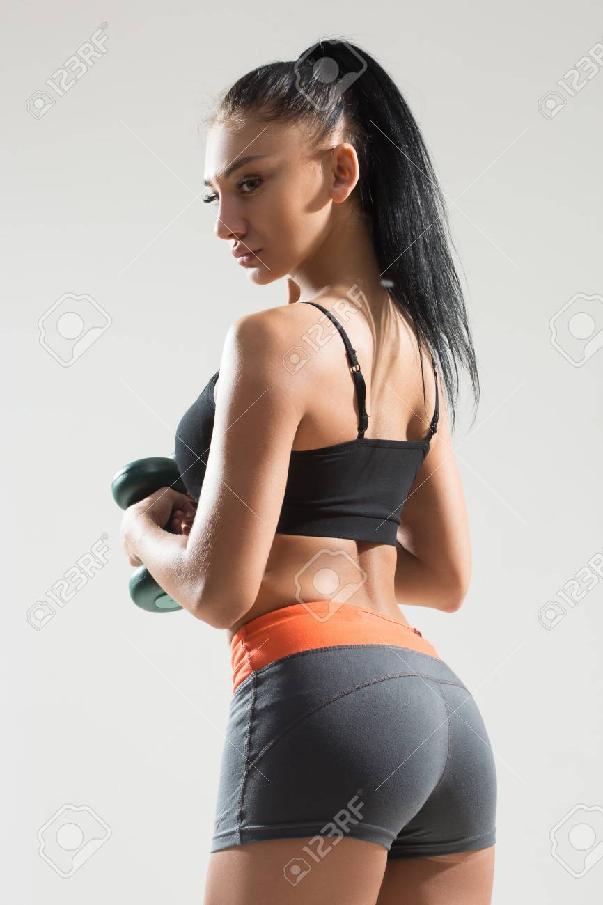 sexy athletic woman with long hair working out with dumbbells