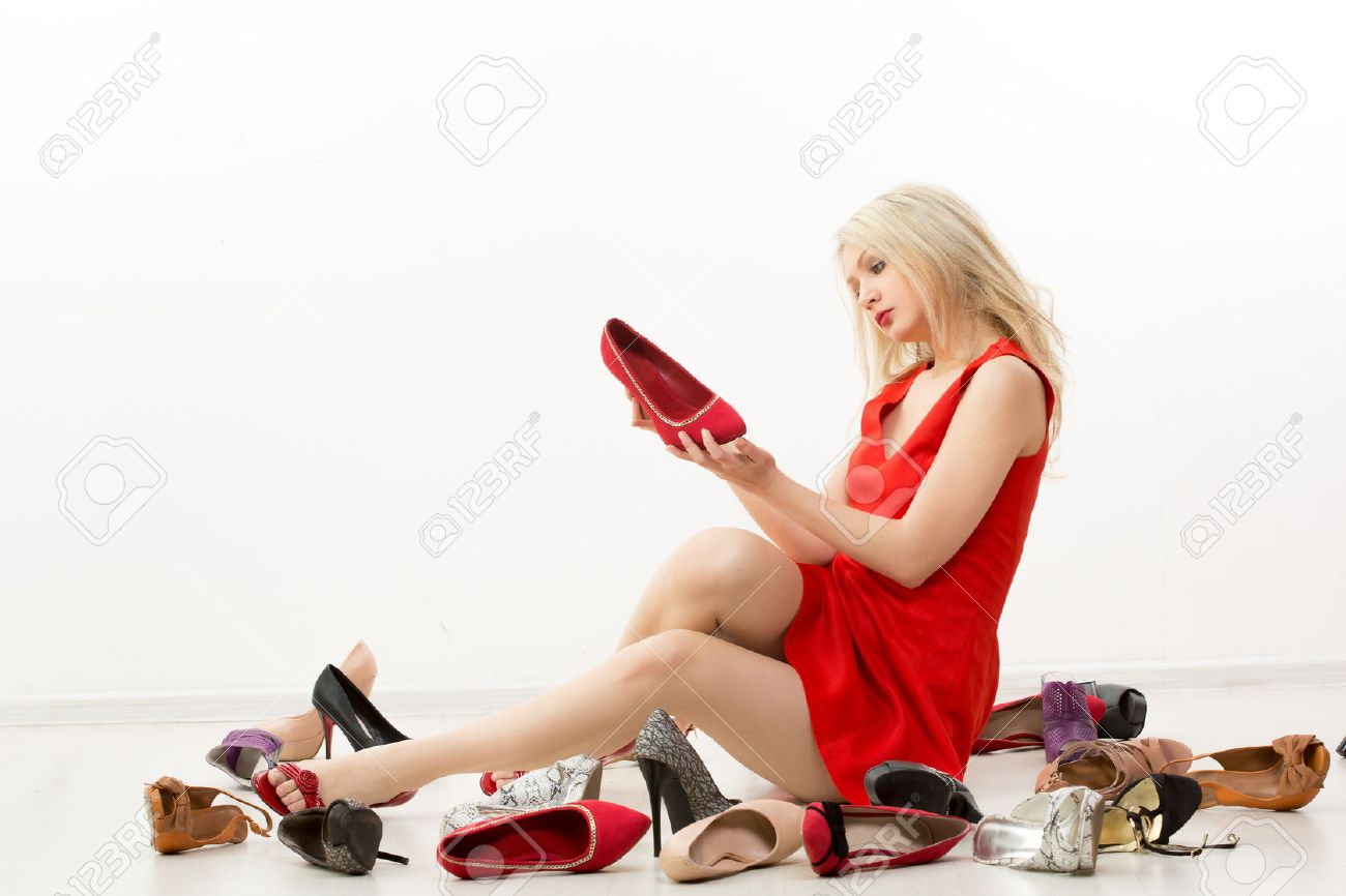 girl in red dress sitting on the floor. Selects shoes. Trying on shoes. - 49142935