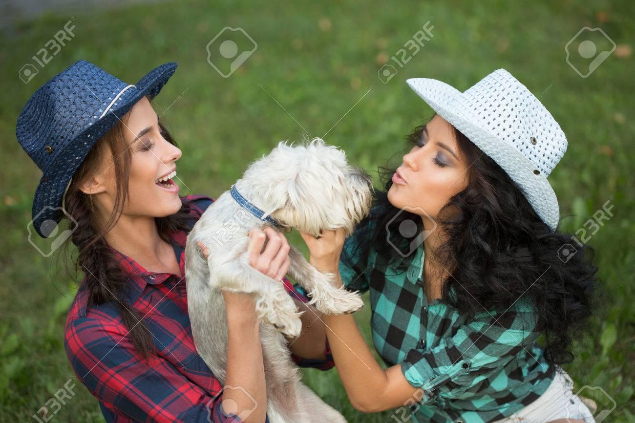 dos chicas paseando con su perro sombrero de vaquero y camisa a cuadros outdoodrs