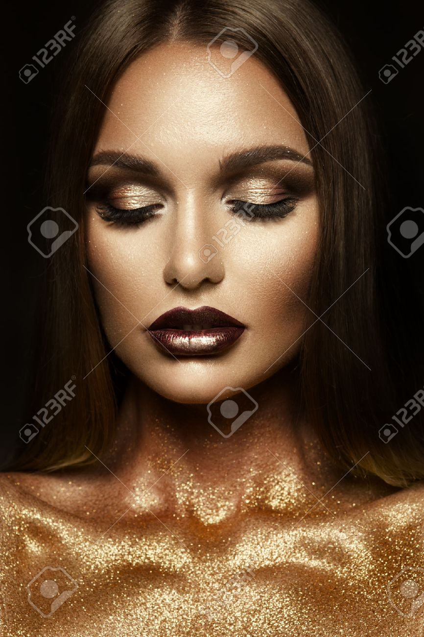 Beautyful girl with gold glitter on her face and body - 62205061