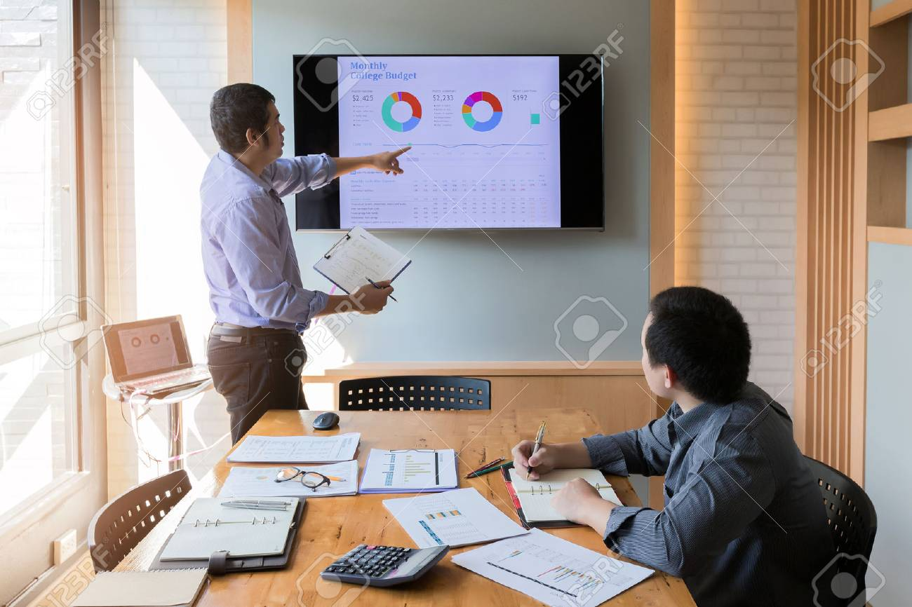 businessman present the monthly college budget in front of tv