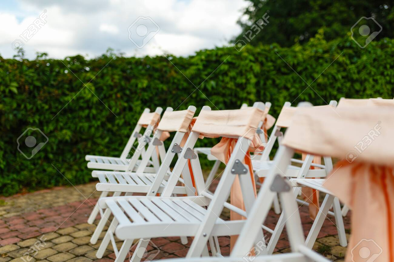 Picture of: White Wooden Chairs Decorated With Orange Bows And Roses For Stock Photo Picture And Royalty Free Image Image 121722130