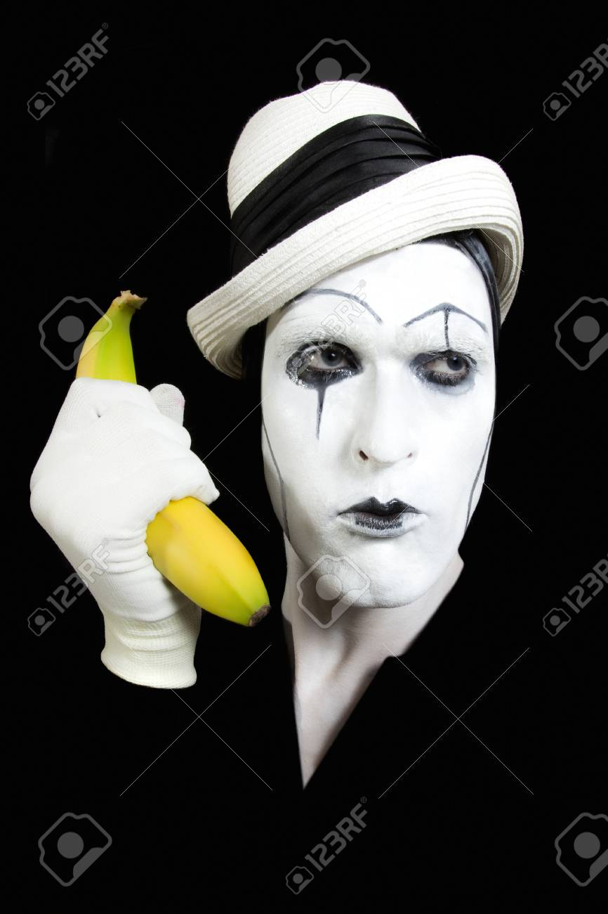 portraits of the mime in white hat holding a banana in his hand Stock Photo - 9418641