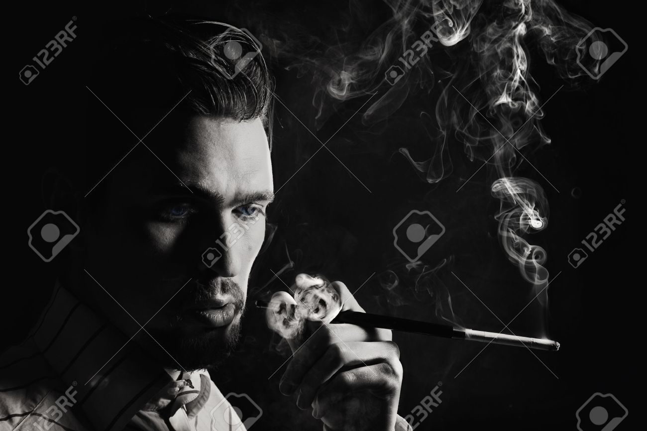 Studio portrait of a young man smoking a cigarette on a black background Stock Photo - 9553667