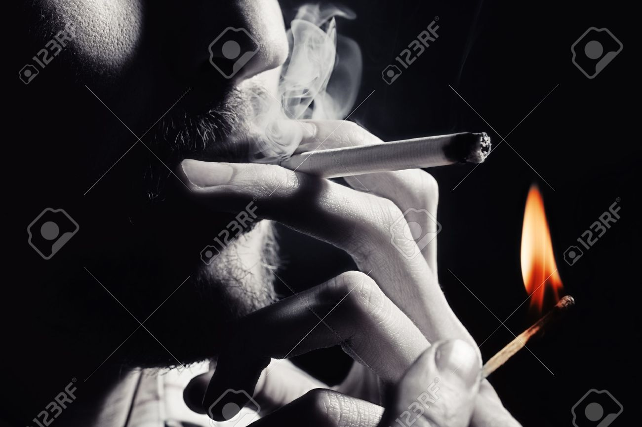 Men's hand lights a cigarette with a match closeup Stock Photo - 9771059