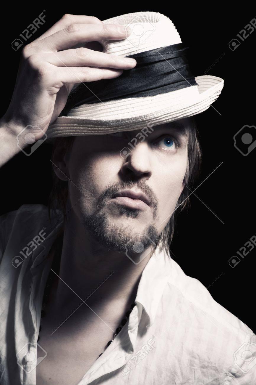 6bdfb24abc92c Banque d'images - Studio portrait d'un beau jeune homme avec un chapeau  blanc à la main sur un fond noir