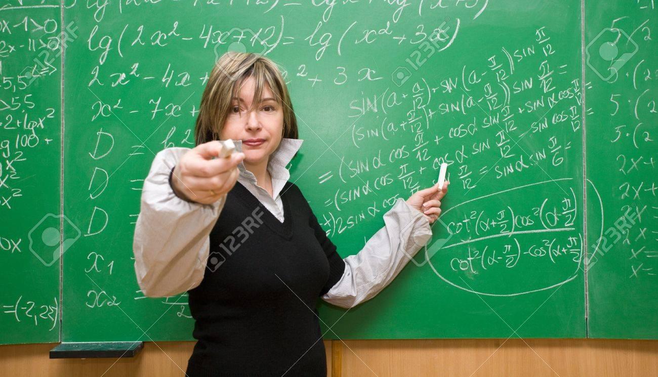 Profesor feliz con el libro de texto gesticulando y haciendo preguntas en el aula de la escuela Foto de archivo - 12082461