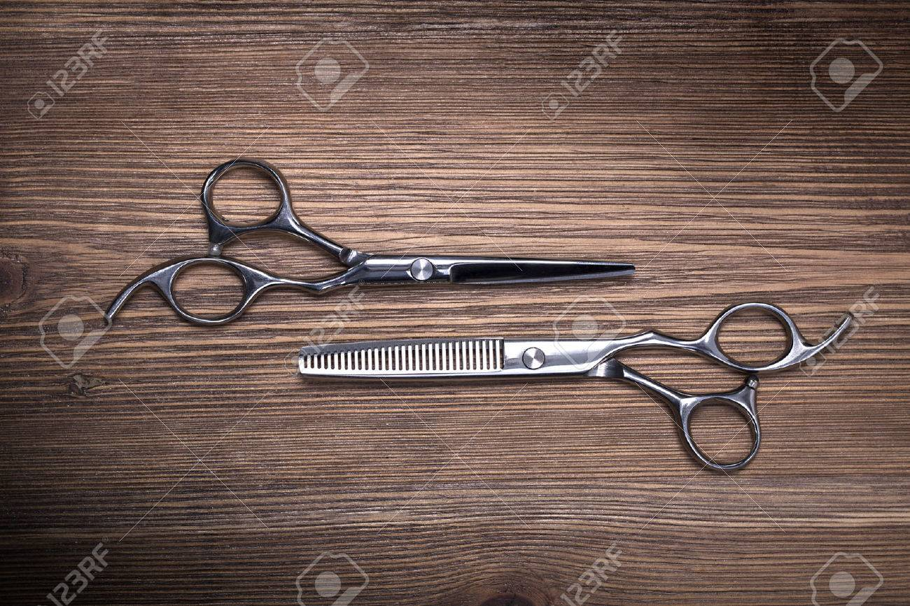 hairdressing equipment like different scissors on brown wooden table in professional hairdressing salon - 52626623