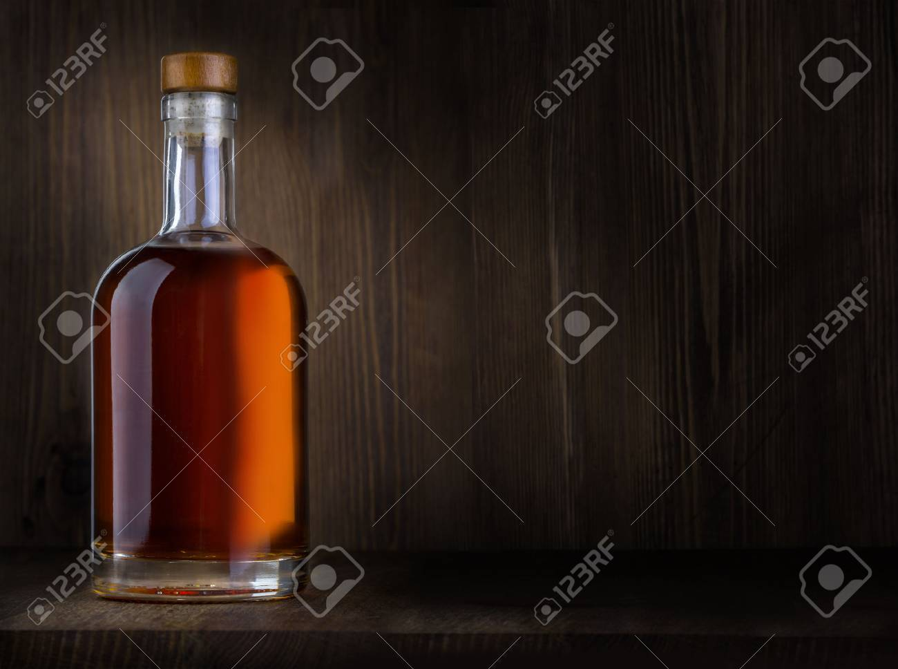 Bottle of whiskey on a wooden background with copy space - 54425522