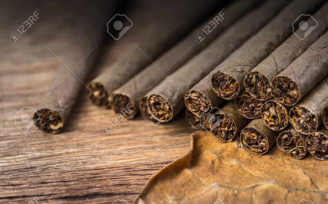 Cigarillo on wooden background close up with tobacco leaf selective focus - 69573784