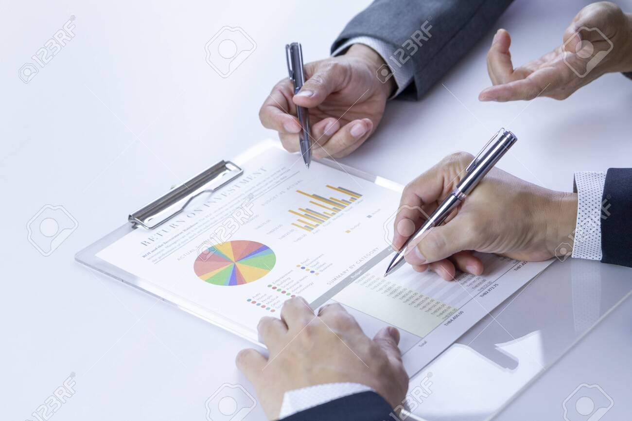 Two businessmen or analysts reviewing financial statement report on Return on Investment, ROI, or investment risk analysis and business performance. - 123735936