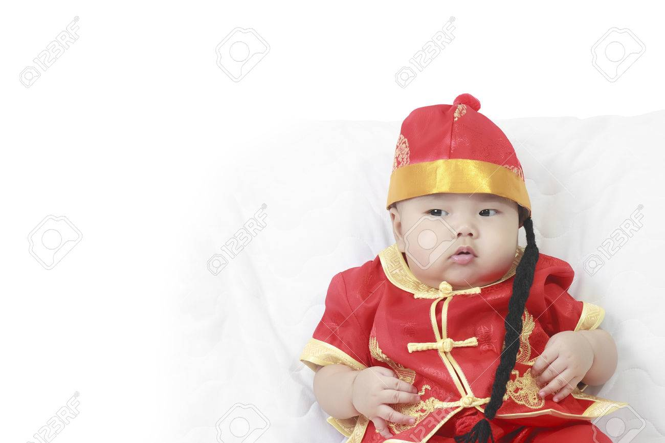 c58728fd1 Asian baby boy wearing red Chinese suit or clothes with hat sit on white  bed or sofa wait for red envelope reward or angpao at Chinese New Year  festival ...