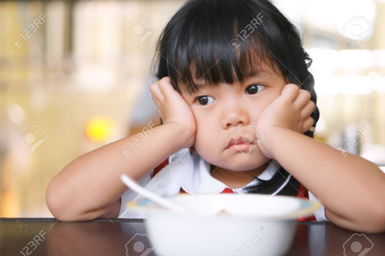 Asian children cute or kid girl student anorexia or sad with vacant and prop up or hand to cheek on food table for breakfast before going to school for study - 106606344