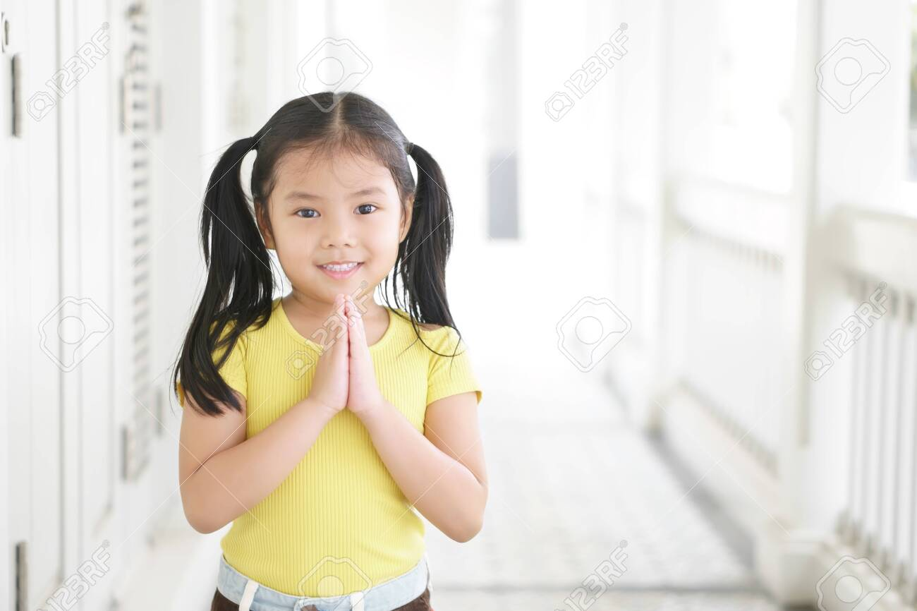 Asian child smiling hand in hand or kid girl pay obeisance and pray or hello welcome and thank you with wear yellow shirt in morning at church or temple for peace on white and receptionist at hotel - 153028537