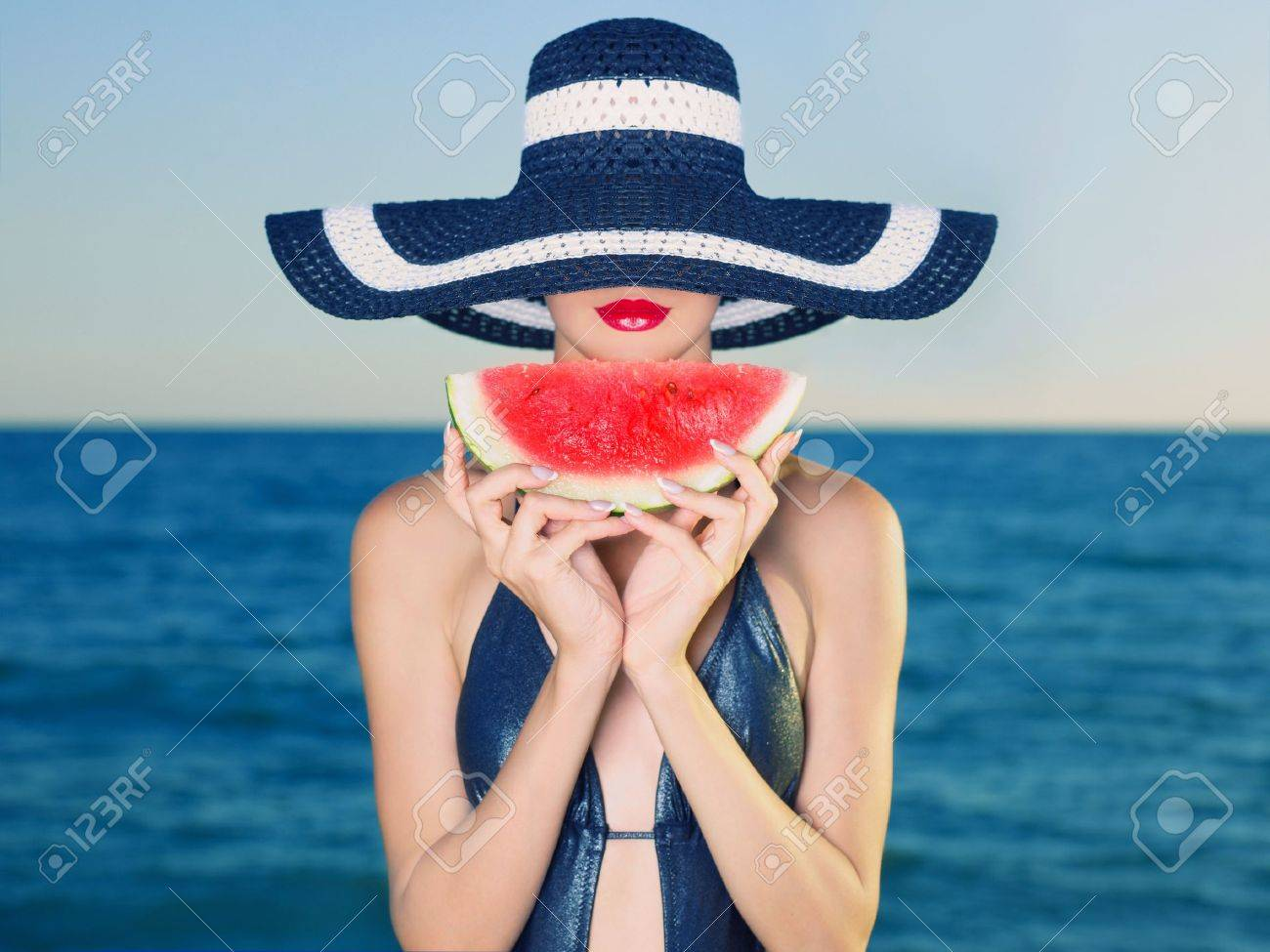 Young stylish lady in a hat at sea with watermelon - 12949677