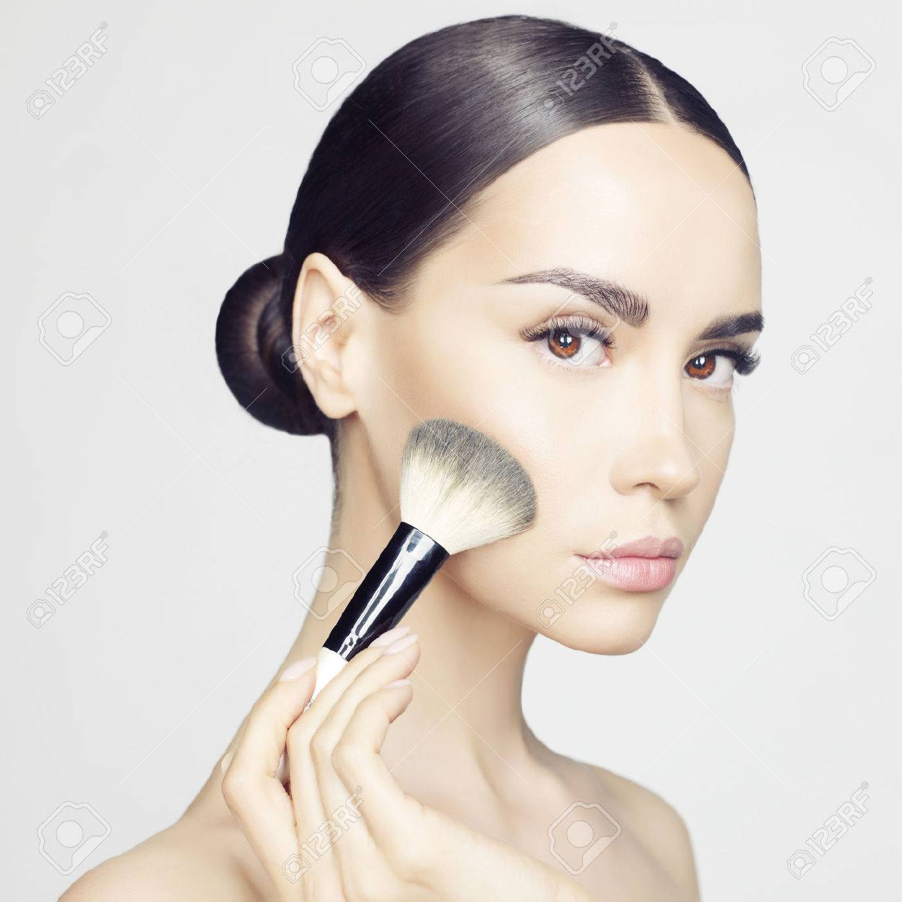 Studio fashion photo of beautiful young lady applying blush. Beauty and care. Extension eyelashes. Spa salon. Perfect face makeup - 42194132