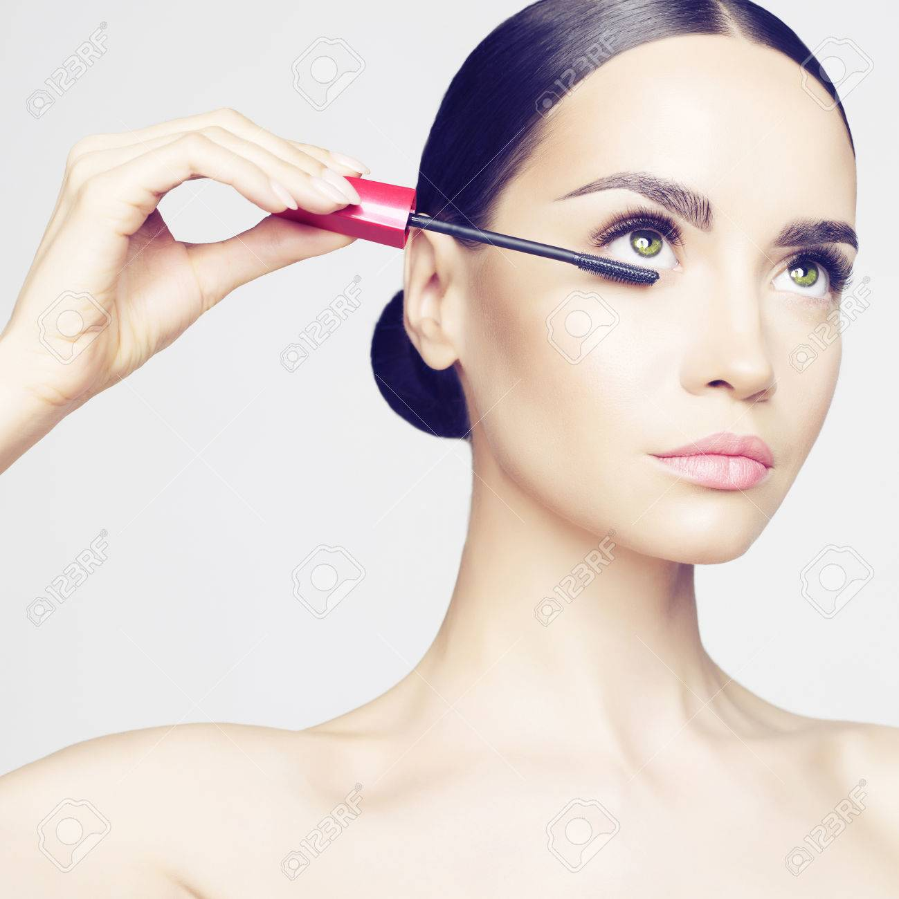 Studio fashion photo of beautiful young lady applied mascara. Beauty and care. Extension eyelashes. Spa salon. Perfect face makeup - 42194133
