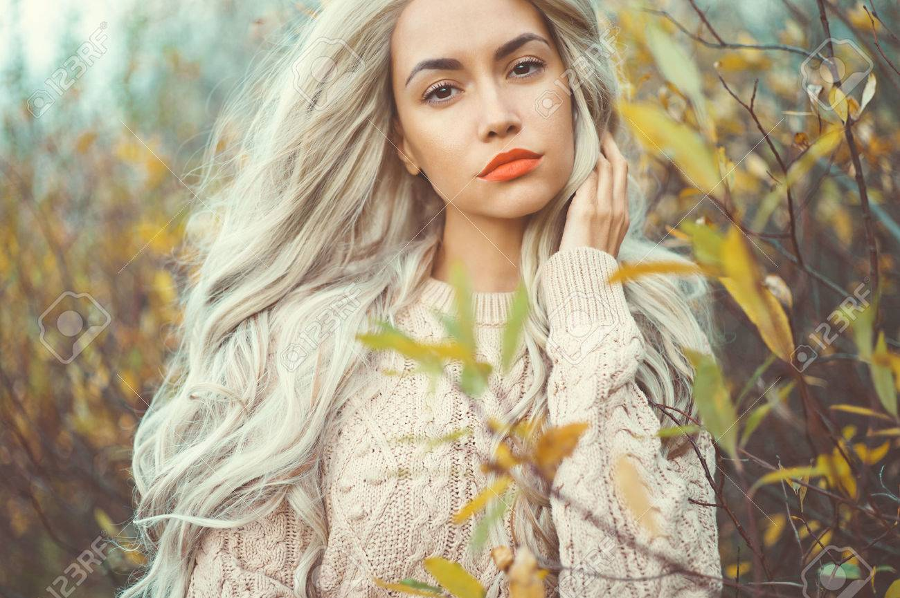 Outdoor fashion photo of young beautiful lady surrounded autumn leaves - 54293964