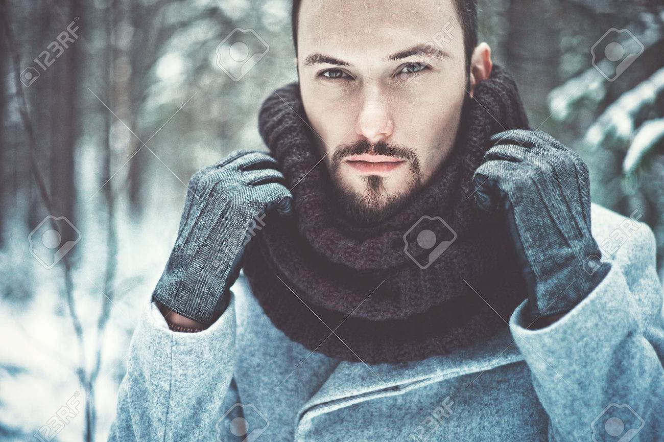 Outdoor portrait of handsome man in coat and scurf. Casual winter..
