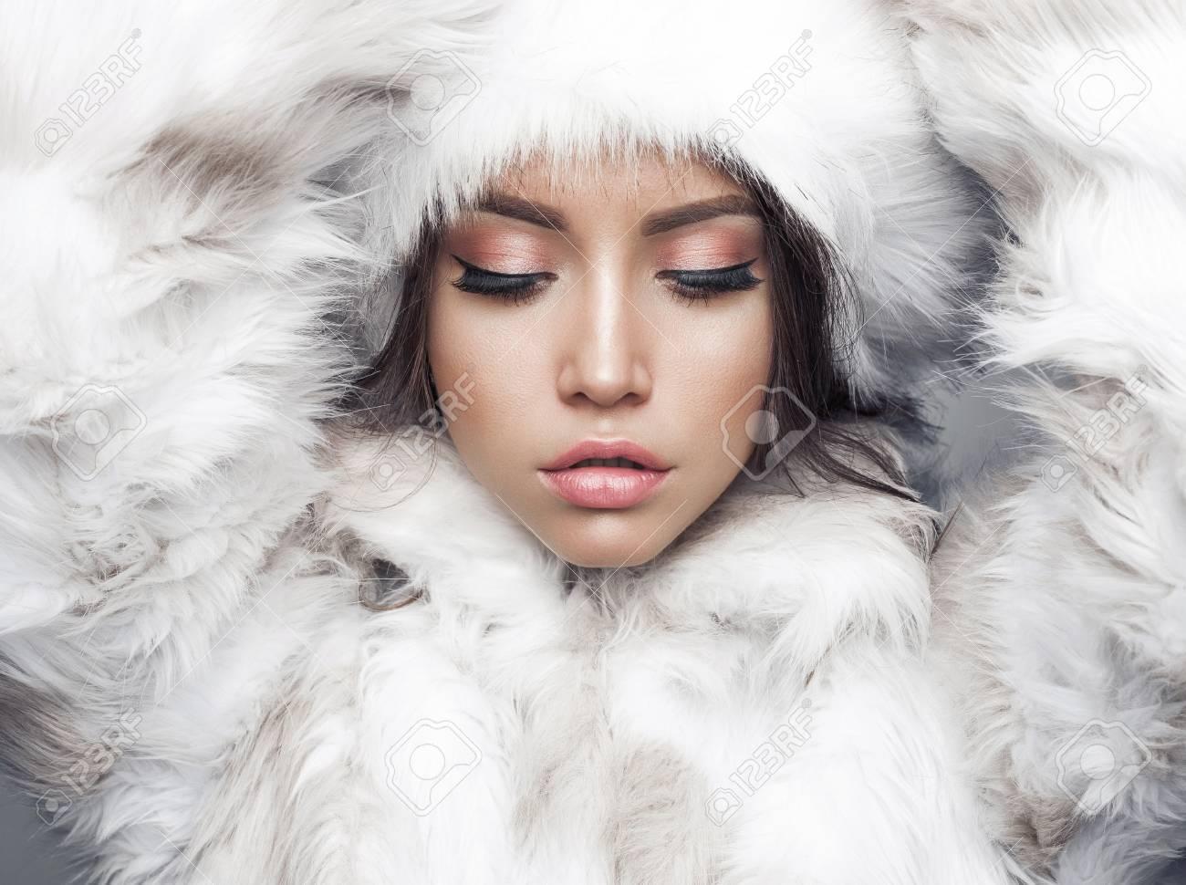 Fashion studio portrait of beautiful lady in white fur coat and fur hat. Winter beauty in luxury. Fashion fur. Beautiful woman in luxury fur coat. Fashion model posing in eco-fur coat and eco-fur hat - 88772988