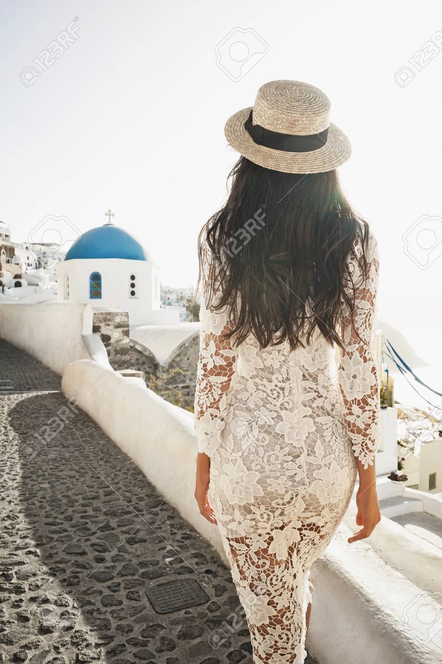 467810d847 Happy woman in white dress and straw hat enjoying her holidays on Santorini  island. Europe
