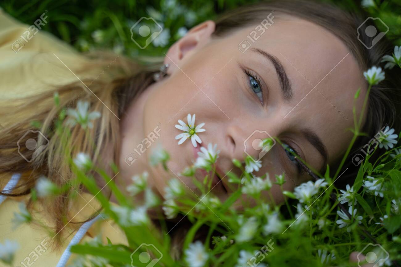 Beautiful young woman lying on the grass against the background of flowers in the forest - 148154115