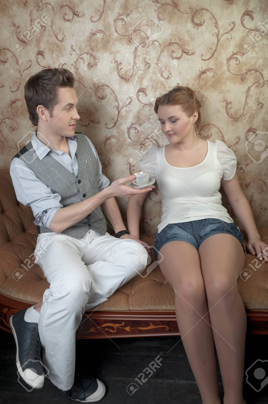 The young and handsome man gives coffee a charming young girl, which lies on the sofa decorated against the wall with wallpaper decorated withornaments Stock Photo - 12600251