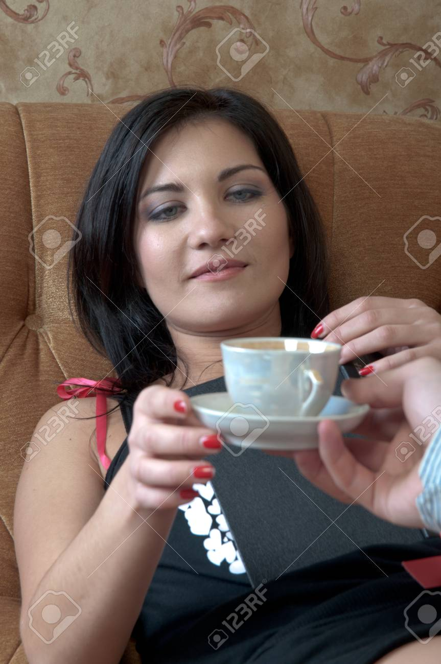 The young and handsome man gives coffee a charming young girl, which lies on the sofa decorated against the wall with wallpaper decorated withornaments Stock Photo - 12600257